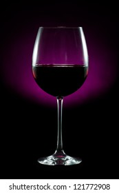 Red wine glass on black and purple background