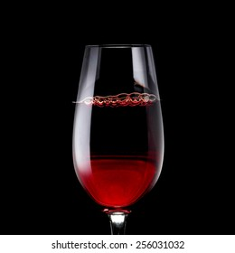 Red Wine Glass on Black Background with Bubbles