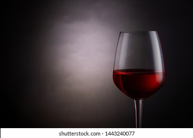 Red wine in a glass on dark background.