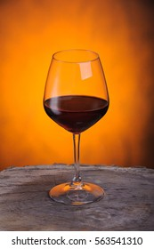 Red wine in a glass on golden background