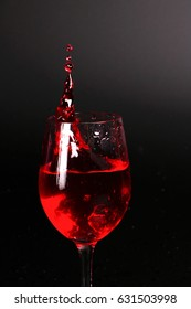 Red wine glass on splash (black background)