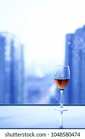 The red wine glass is on the windowsill, the background is blurred urban landscape.