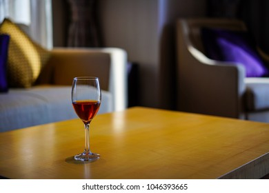 The red wine glass was on the wooden table in the living room.