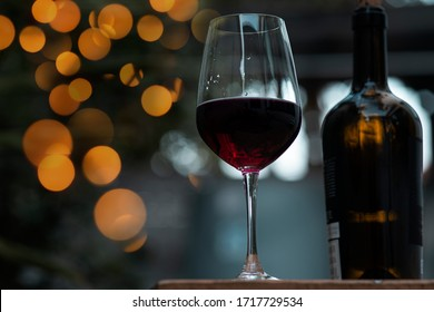 Red wine in glass on wooden bar.
