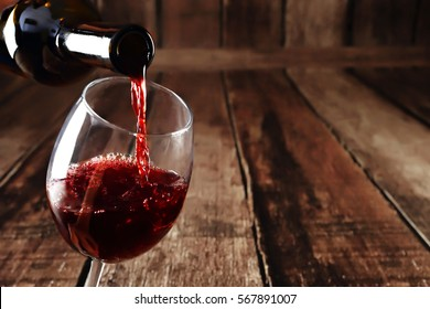 Red wine in glass on wooden background. Beautiful alcohol background. Red wine pouring from bottle. Free space for text on wooden backdrop.