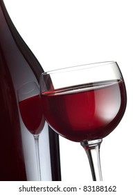 A red wine glass with reflection on a bottle