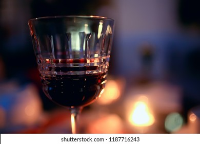 red wine glass serving / romantic dinner in the interior of the restaurant, a table served with a glass of grapes wine