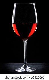 Red wine glass silhouette over black background