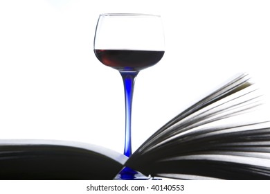 A red wine glass is standing behind an open book. Isolated on white. Studio shot.