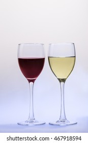 Red wine glass and white wine glass isolated on a light-blue background
