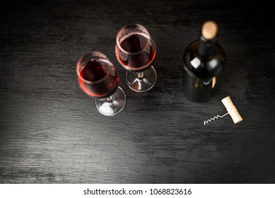 Red wine glasses and bottle on black wood background. Top view with copy space