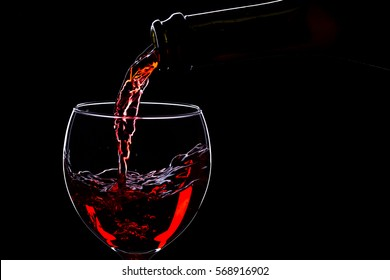 Red wine in wine glasses and wine bottle on a black background, silhouette, minimalism, studio lighting