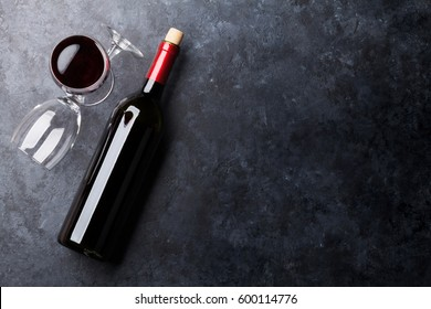 Red wine glasses and bottle on stone background. Top view with copy space