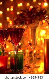Red wine in glasses, candle lights, flowers and twinkle lights on background.