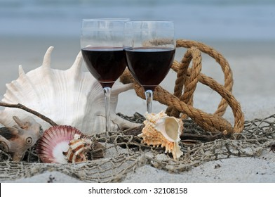 Red Wine Glasses on the Beach Surrounded by shells, sand and nautical objects
