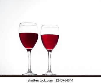 red wine glasses on table, isolated on white background