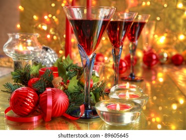Red wine in glasses,baubles,candle lights,green twig and twinkle lights on golden background.