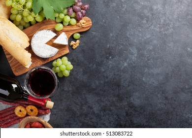 Red wine grape, cheese, bread and sausages over stone table. Top view with copy space