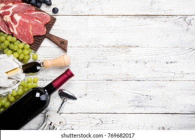 Red wine, grape, cheese camembert, prosciutto meat on white wooden background. Appetizer, gourmet, romantic concept. Top view, copy space