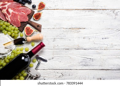 Red wine, grape, figs, cheese camembert, prosciutto meat on white wooden background. Appetizer, gourmet, romantic concept. Top view, copy space