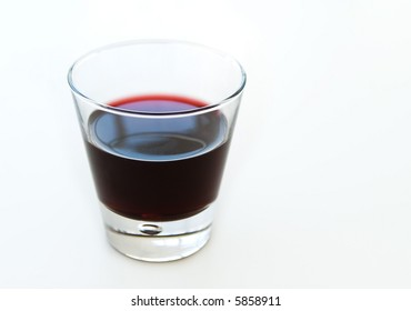 red wine or grape juice glass overlit on white background