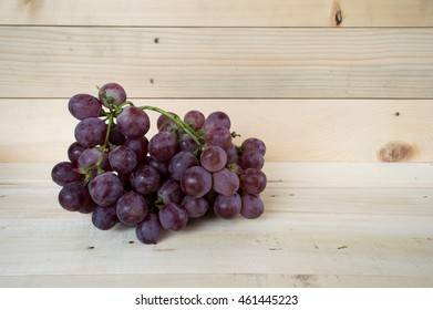 Red wine grapes on wood background.