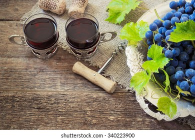 red wine and grapes. Wine and grapes in vintage setting with corks on wooden table toning
