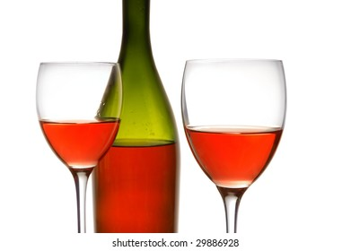 Red wine and green bottle on white
