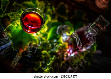 Red wine and green ivy on a wooden table in front of a wooden background with a creative lighting