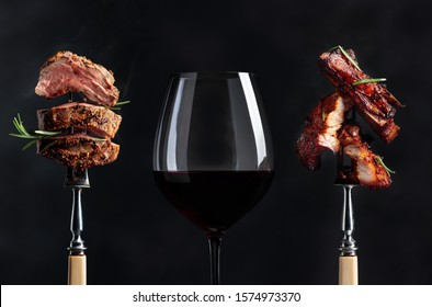Red wine and grilled meat. Grilled pork belly and beef steak with rosemary on a black background. Copy space.