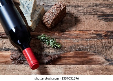 Red wine and ingredients for romantic dinner on the wooden background. Cheese and bread.