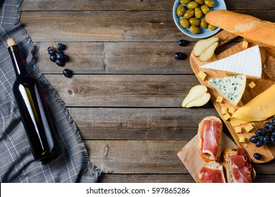 Red wine and ingredients for romantic dinner. Black grape, olives, halves of pear, ham meat, cheese and bread. Wooden background, copy space in the middle of photo.
