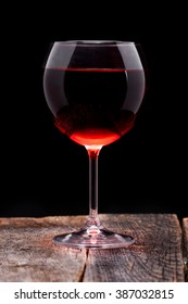 Red wine into the glass in wooden table