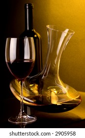Red wine , wine jug and wine glass. Black wine bottle at back. Low yellow background light.