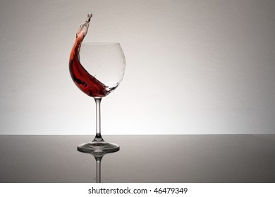Red wine leaping and splashing from a wine glass.