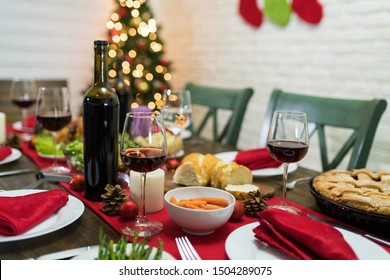 Red wine with meal arranged on dining table at home during Christmas dinner party