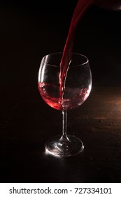 Red wine in motion on black background. Alcohol advertising closeup, exquisite beverage pouring in wine glass. Tasty alcoholic drink, commercial concept