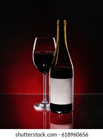 Red wine on glass and bottle on gradient mirror table or background.