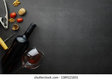 Red wine on a stone background. Wine glass and black wine bottle. Nuts cheese and tomatoes for snack.