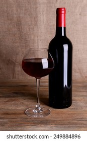 Red wine on table on sack background