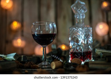Red wine on a wooden table in front of a wooden background with a creative lighting