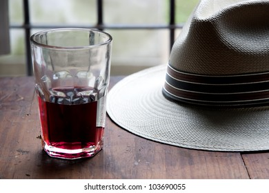 red wine and panama hat over wooden table