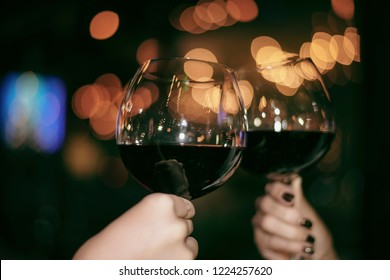 Red Wine Party. Romantic Lesbian Gay Couple Enjoying Dinner at Home, Love, Relationship, Romantic Concept. Happy Celebrating and Making Cheers with Glasses of Red Wine Against Blurred Bokeh Night Club