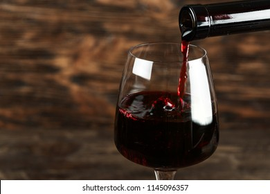red wine pour into a glass on a wooden background, space for text