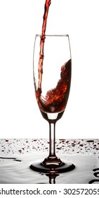 Red wine poured in a glass on white background