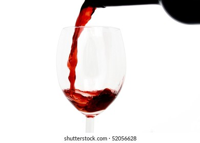 Red wine poured into a glass isolated on white background