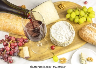 Red wine poured into a glass at a tasting, with various types of cheeses, bread, and grapes. Selective focus