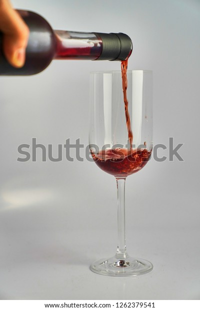 Red wine poured into slim wine glass