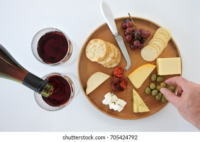 Red wine poured into two wineglasses and mans hand selecting an olive  from a cheese platter. Food background. Copy space