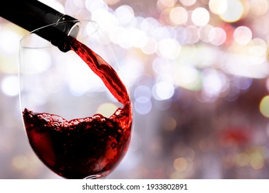 Red wine pouring from the bottle in glass